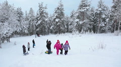 Group of Russian children climbing the mountain on the snow while tubing Stock Footage