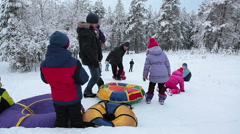 Children and adults relax on slope, group of kids slide downhill on a tubing Stock Footage