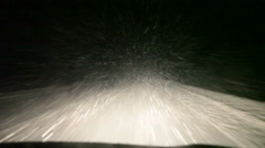 Snow flying at windshield while car driving at winter night Stock Footage