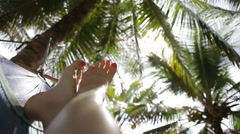 Feet swinging in a hammock, POV. Relaxing under palms on the beach at sunset. - stock footage