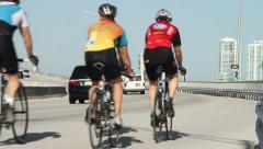Group of cyclists go up bridge with city skyline in back ground Stock Footage