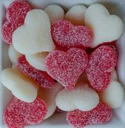red and white gummy hearts in bowl on white - stock photo