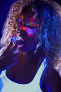 Beautiful curly girl posing in ultraviolet light Stock Photos
