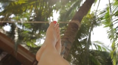Feet swinging in a hammock, POV. Relaxing under palms on the beach at sunset. Stock Footage