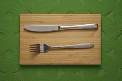 Modern cutlery set on green fabric background Stock Photos
