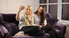 Two girls take a selfie on the sofa Stock Footage