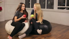 Two girls sitting on bag chairs and eat apples Stock Footage