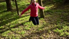 Cheerful blue eye ponytails blonde teen girl running and jumping at park Stock Footage