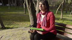 Beautiful brown hair green eye woman thinking holding using tablet park Stock Footage