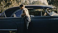 USA 1950s: boy loading grocery in the car Stock Footage