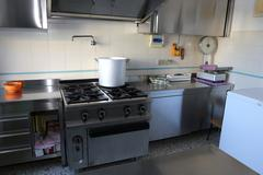 Industrial kitchen with big gas stove and the giant aluminum pot Stock Photos