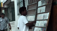 Dominican Republic La Romana Caribbean Sea 041 young guy prepares DVD's to sell Stock Footage