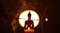 Buddha statue and candle with hand holding incense Stock Footage