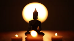 Replica of Buddha statue and moving candle flames Stock Footage