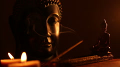 Two Buddha statue with candles and smoke of incense Stock Footage