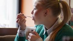 Girl in cafe eat latte foam Stock Footage