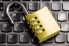 Open combination padlock on a laptop keyboard symbolizing data security - stock photo