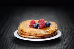 pancakes with berries and maple syrup, on wooden table - stock photo
