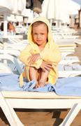Child in a dressing gown on rug. - stock photo