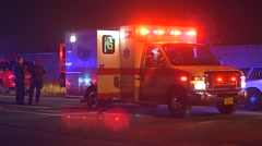 Ambulance on scene and police and medical responding to a car crash Stock Footage