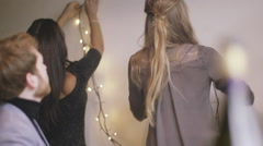 Young men and women decorating wall with fairy lights Arkistovideo