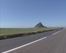 Road to Mont Saint-Michel at the French coast + pan salt marshes + pan to  left Stock Footage