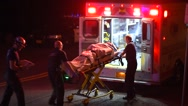 Stock Video Footage of Medics Loading Patient Into An Ambulance For Transport To A Hospital
