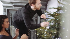 Young man and woman decorating Christmas tree Stock Footage