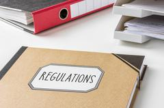 A folder with the label regulations Stock Photos