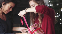Young women wrapping Christmas gift Stock Footage