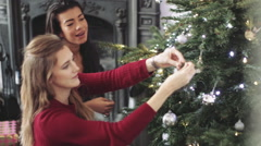 Young women decorating Christmas tree Stock Footage