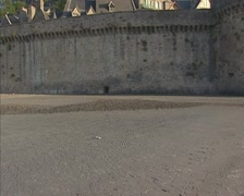 Low tide Mont Saint-Michel Bay tilt up walled settlement on rocky islet Stock Footage