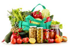 Green shopping bag with groceries isolated on white background Stock Photos