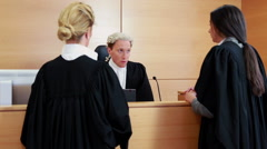 Two lawyers standing and speaking with the judge Arkistovideo