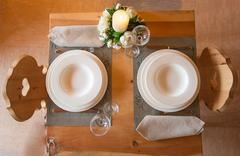 table set in mountain chalet for two people - stock photo