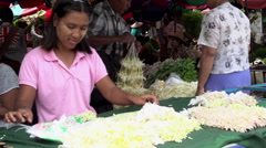 Mandalay, girl with tanaka on face makes flower bouquet Stock Footage