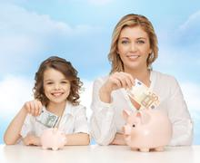 Mother and daughter putting money to piggy banks Stock Photos