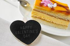 Happy valentines day in a heart-shaped chalkboard and a piece of cake Stock Photos