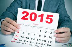 young businessman with a 2015 calendar - stock photo