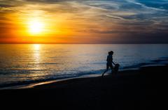 Girl runs with the dog on the beach Stock Photos