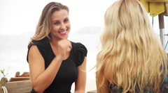 Mother and daughter talking at a cafe on the beach Stock Footage