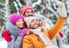 smiling friends with camera in winter forest - stock photo