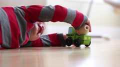 A little boy plays with toy wood truck Stock Footage