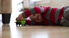 Little boy plays with his toy wood truck Stock Footage
