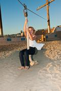 Beautiful blond Latina girl enjoying the beach zip line ride. Stock Photos