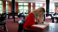 Mature student with reading glasses studying at library desk Stock Footage