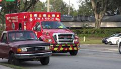 Red Fire Rescue Ambulance Races Down Busy Street Pass Cars & Trucks W/ Audio 4K Stock Footage