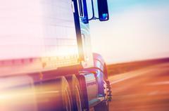 Speeding american semi truck on the highway. Stock Photos