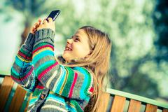 Happy teenage girl taking pictures using her modern smartphone device. Stock Photos