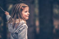 Little caucasian girl playing with small stick. vintage purple color grading. Stock Photos